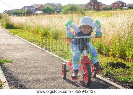 Small Boy Rides A Tricycle On A Track In The Suburb