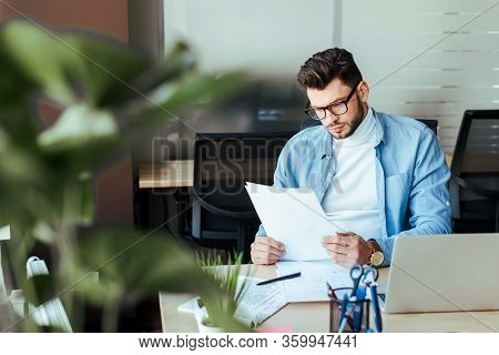 Selective Focus Of Concentrated It Worker Looking At Papers At Table In Coworking Space