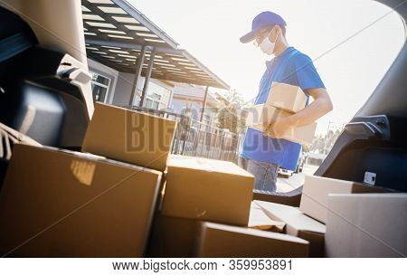 Asian Delivery Man Wearing Mask Send A Package Holding Smartphone On Front Receiver Shipping Deliver