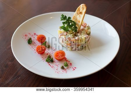 Russian-style Salad On White Plate On Wooden Table