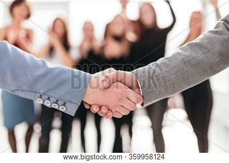 Close Up. Business Handshake On A Blurred Background Of The Business Team