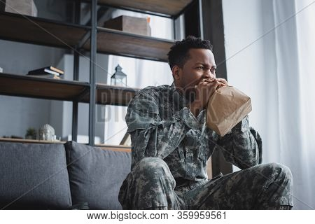 Stressed African American Soldier In Military Uniform Breathing With Paper Bag While Having Panic At