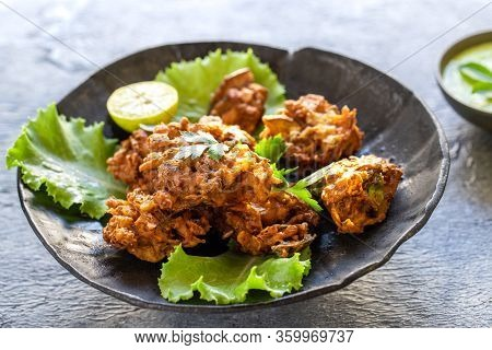 Indian Cuisine Indian Food. Pakora Traditional Indian Deep-fried Snack. Pakoras On Black Plate With