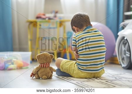 Sad Boy Sits On The Floor Of The Nursery. Lonely Kid Misses Home