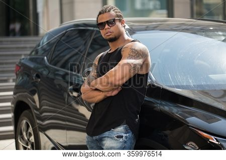 Black Man In Sunglasses Standing Near The Car With Modern Building On Background.