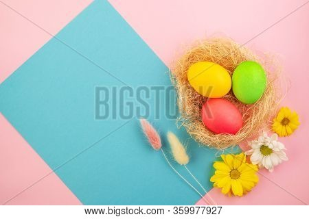 Beautiful Spring Composition Of Colored Easter Eggs And Fresh Flowers On A Pink And Blue Pastel Back