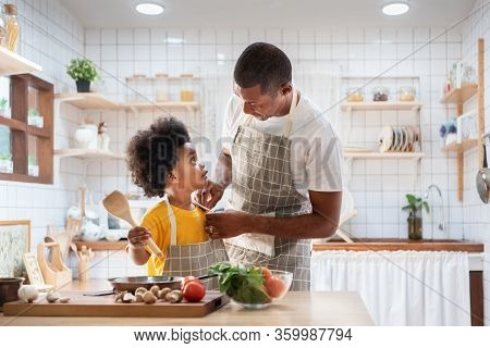 Happy African Father And Son Dress Up Together Before Cooking In The White Kitchen. Single Dad Chef