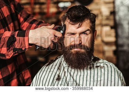 Bearded Handsome Man Visiting Hairstylist. Barber Shop. Barber Shearing Beard To Man. Male Hairstyli