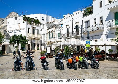 Italy, Bari, August, 2017 - View Of The Sunny Street Of Bari With White Houses And And Parked Scoote