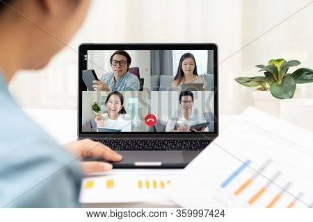 Back View Of Business Woman Talking And Discussion In Video Conference. Asian Team Using Laptop And