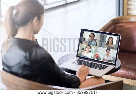 Back View Of Business Woman Talking About Sale Report In Video Conference. Asian Team Using Laptop A