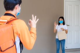 Asian Woman Pick Up Delivery Food Bag From Door Knob And Ok Sign For Contactless Or Contact Free Fro