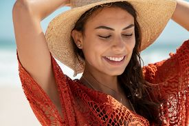 Carefree young woman at beach enjoying summer holiday. Portrait of happy smiling hispanic woman relaxing at sea during vacation. Close up face of beautiful fashion girl with dress walking on the beach