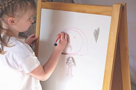 Cute Little Blond Girl Drawing On White Board. Girl Drawing Happy Smiling Woman With Markers. Close