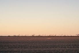 Plowed Field In The Sunset At Dawn With A Clear Sky Over A Beautiful Countryside