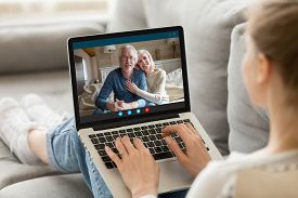 Elderly Grandparents Communicating With Adult Granddaughter Using Video Call App