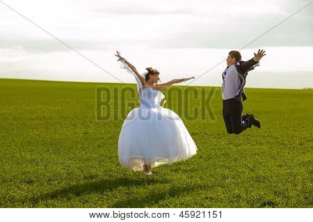 Russia newlyweds jump couple, bride and groom jumping in a green