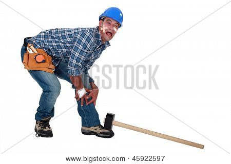 Builder dropping hammer on foot