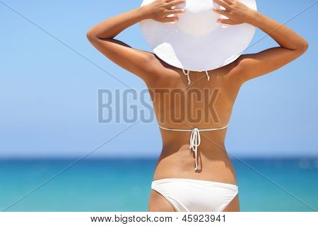 Travel woman on beach enjoying blue sea and sky wearing white beach sun hat and bikini. Beautiful pretty stylish young asian model from behind on vacation holidays.