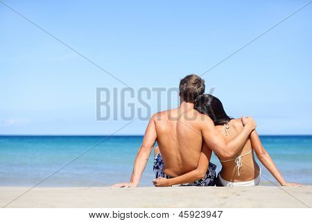 Happy young couple in love relaxing on beach vacation enjoying ocean view together sitting in the sand embracing and hugging. Beautiful young multiethnic couple, Asian woman, Caucasian man.