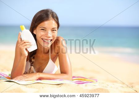 Sunscreen woman showing suntan lotion bottle. Beautiful smiling happy asian woman with suntan cream in plastic container lying on beach during summer travel vacation. Mixed race female model.