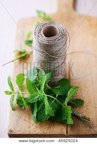 Fresh mint and kitchen twine on a chopping board