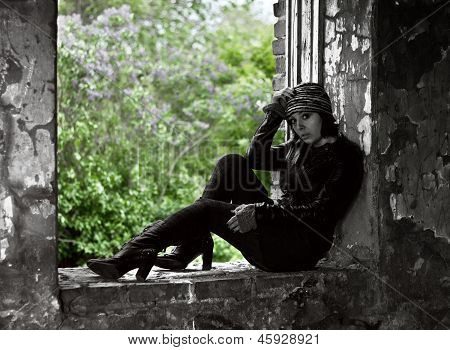 Woman in grunge style sitting on window with lil