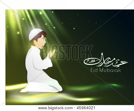 Arabic Islamic Calligraphy of text Eid Mubarak with Muslim boy in tradition outfits reading Namaj ( Islamic Prayer) on shiny green background. poster