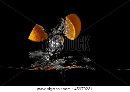 Two orange slices splashing into fluid