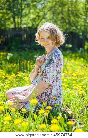 Young Pregnant Woman Sit Down On Grass With Yellow Flowers