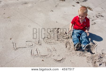Young Boy Writing In Sand.