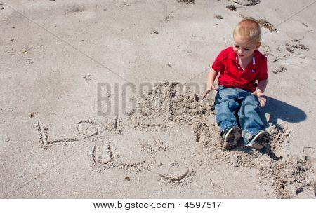 年轻的男孩在沙子中写作。