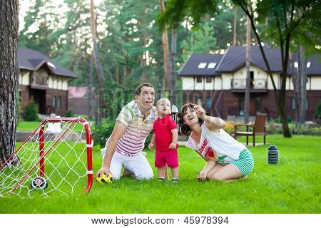 Small Boy Plays Football With Parents In Park