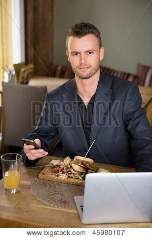 Portrait of young business man with mobilephone and laptop having meal in restaurant