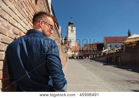 back view of a casual young man standing next to a brick wall in Sibiu city, Romania, near the Council  Tower