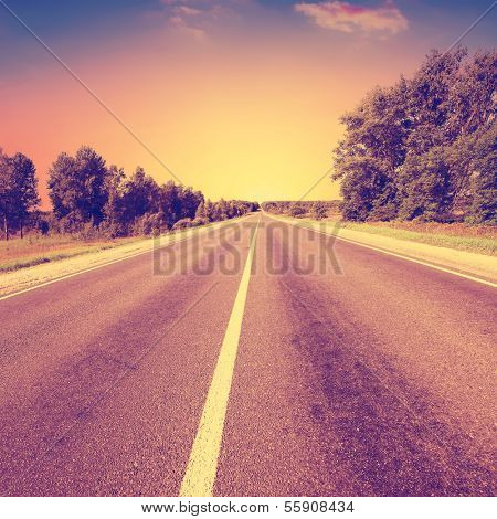 Vintage photo of country asphalt road.