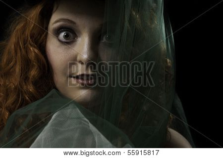 Young woman with wide eyes and green veil