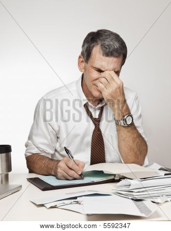 Man With Headache Paying Bills