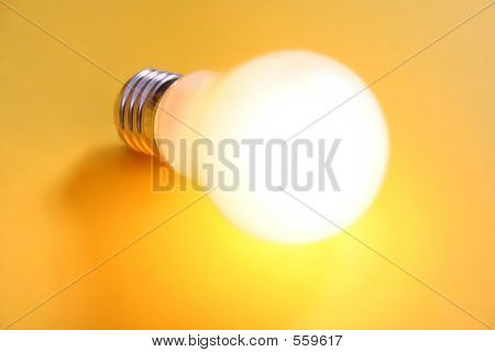 Illuminated Lightbulb On Yellow Background