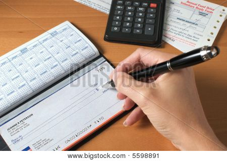 Writing A Check To Pay The Bills Hand Holding Pen