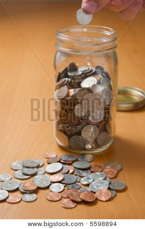 Putting Coins Into A Jar