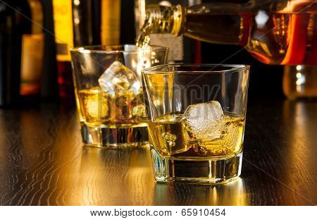 Barman Pouring Whiskey Behind Whiskey Glass