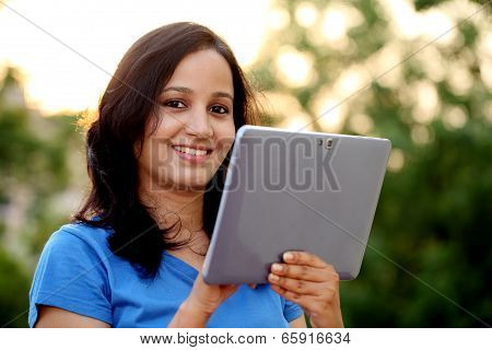 Young Woman Using Tablet Computer At Outdoor