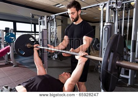 Bench press weightlifting man with personal trainer in fitness gym