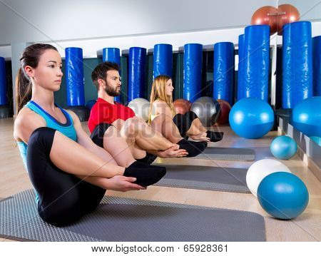 Pilates people group the seal exercise man and women at fitness gym