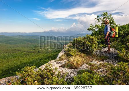 Young hiking man in the rays of sunset, standing at the top of Tope Kermen, Crimea, Ukraine