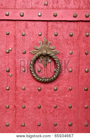 Doorknocker on red entrance door of Winchester Cathedral, England