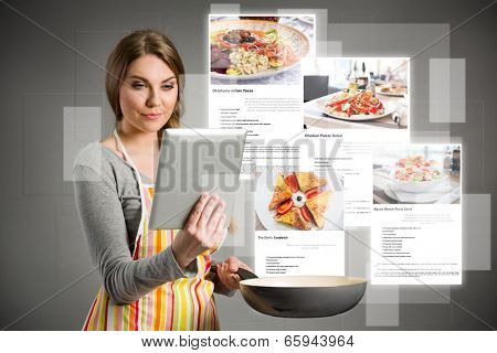 young woman cooking using the tablet, cloud of colorful social media icons out of tablet pc