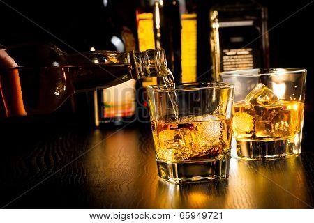 Barman Pouring Whiskey In Front Of Bottles, Focus On Top Of Bottle
