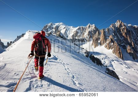 Mountaneer climbs a snowy ridge in Mont Blanc, France. Enterprise, diligence, team work: mountaneering concepts.